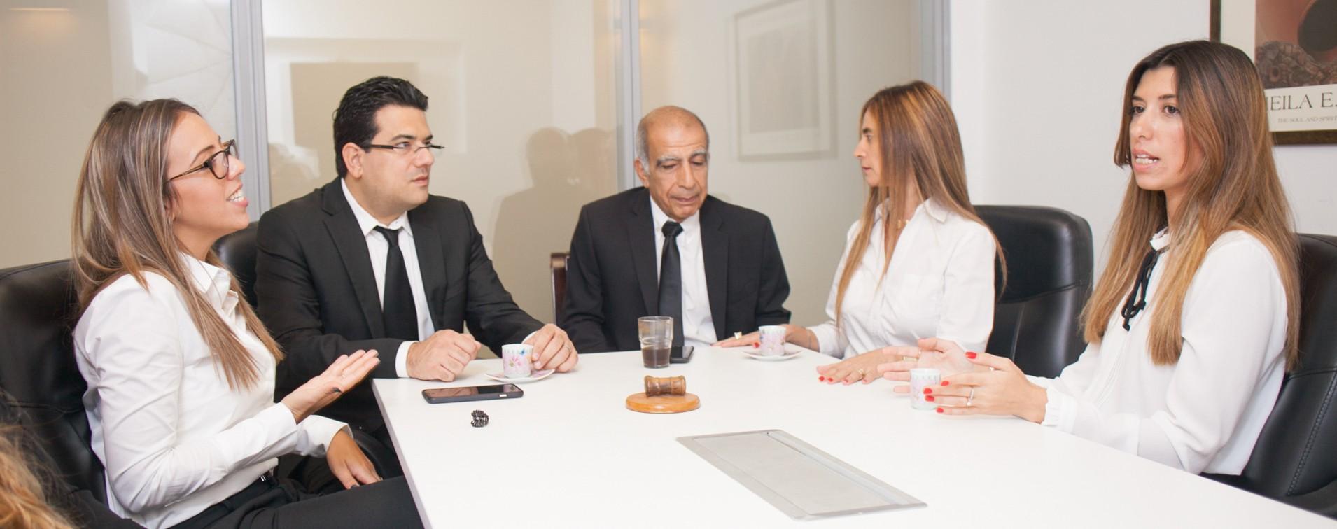 צוות משרד עורך דין גירושין אמיר זבולון יושבים מסביב לשולחן ושותים קפה