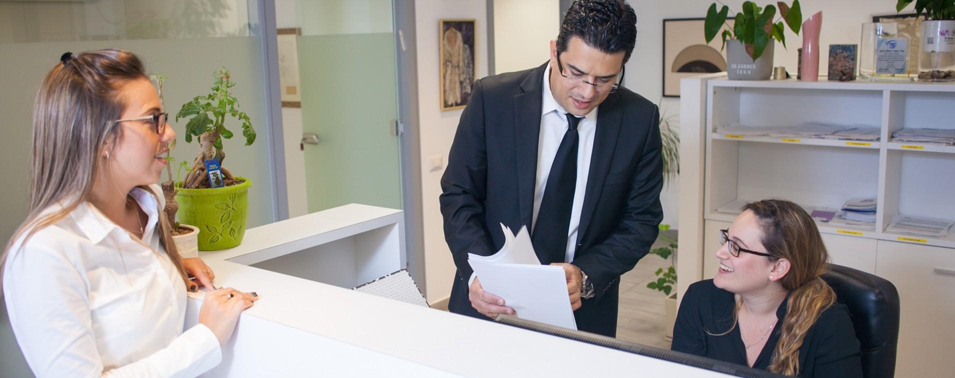 עורך דין אמיר זבולון עובר על מסמכים עם מנהלת המשרד
